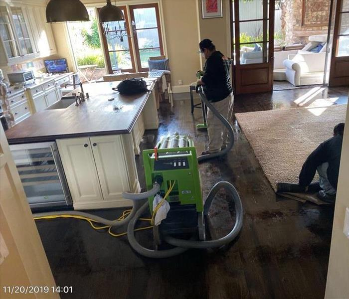 SERVPRO employee doing water extraction from roof leak damages