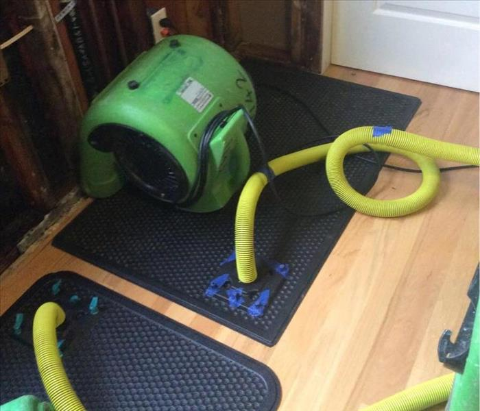 SERVPRO equipment extracting water from wood floor