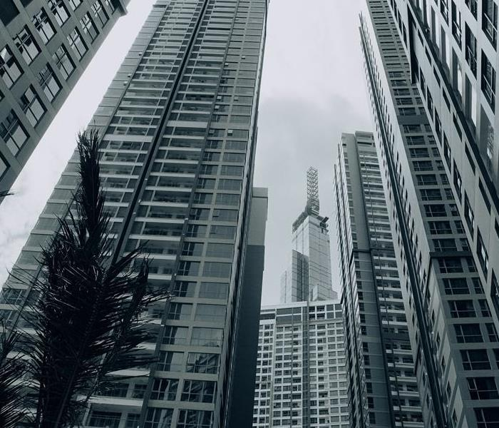 Several high rise buildings loom amongst a grey atmosphere